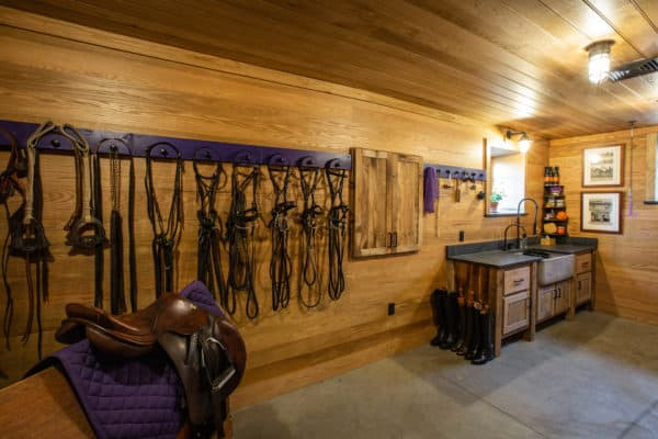 horse barn tack room with equipment hanging on walls and sink in far corner