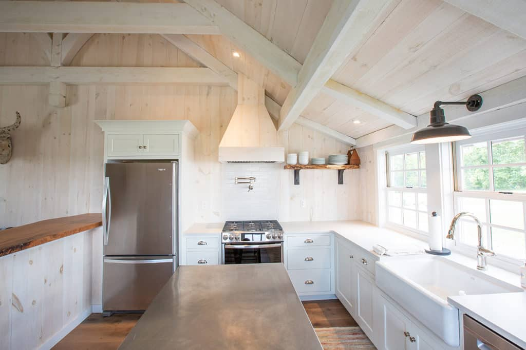 kitchen inside of newly built barn with stainless steel refrigerator